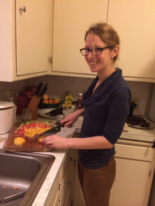 Rachel chopping tomatoes for cucumber tomato salad to go with the Sabih