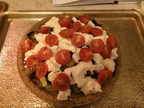 Very full tart with roasted vegetables, cheese, and cherry tomatoes