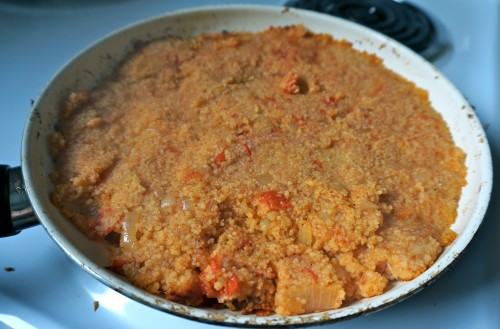Couscous with tomatoes and onion in pan