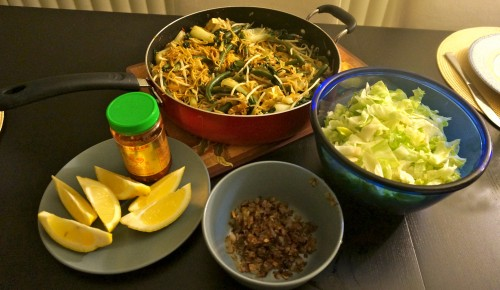 Mee goreng with lettuce, lemon wedges, sambal oelek, and fried shallots