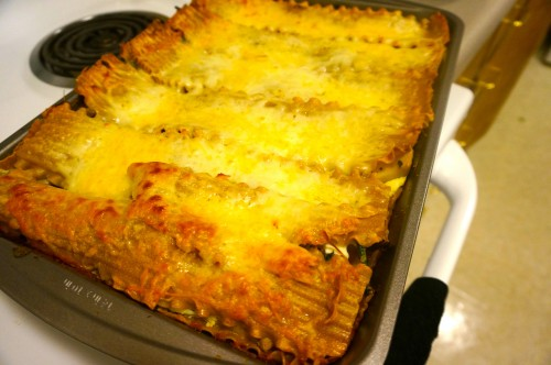 Mushroom lasagna topped with shredded mozzarella and parmesan